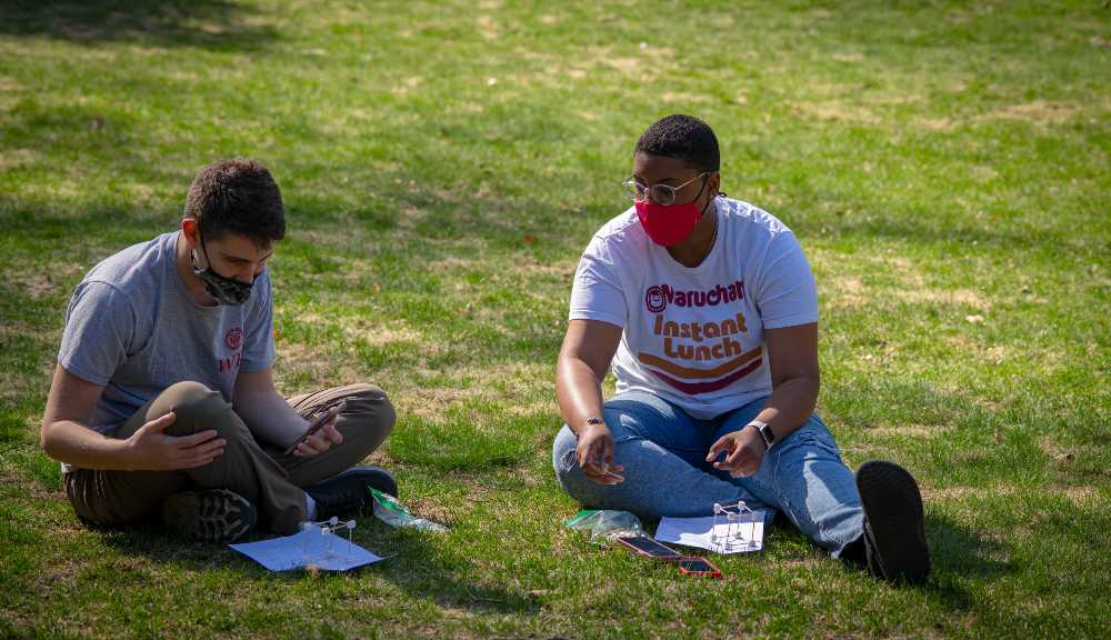 Two students working on a project during an outdoor lab class.