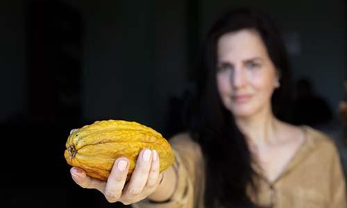WPI alumna holding cacao plant