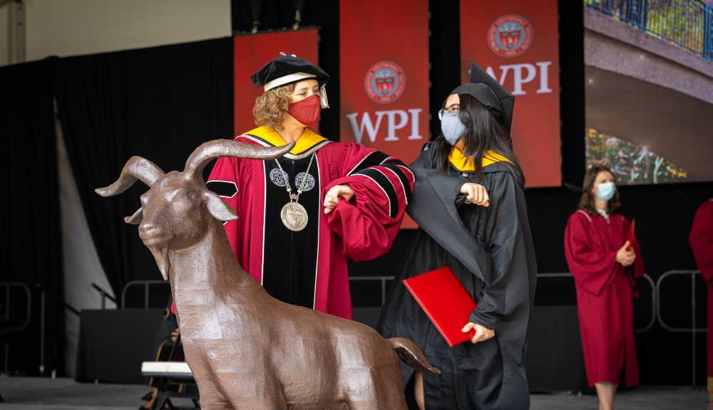 President Leshin shares an elbow bump with a graduating student.