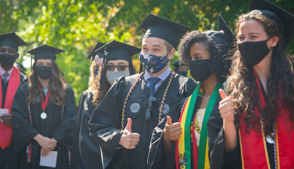 Graduating students smile together and flash thumbs up in their graduating regalia and masks.