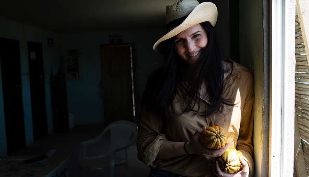 Leila Carvajal smiles while holding cocoa beans up to the camera in a dark room against a window.