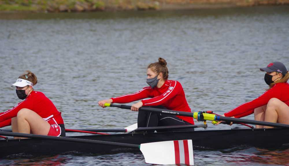 Members of the women's rowing team participate in an event out on the water.