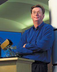 Curt Carlson in a blue shirt  with his arms folded in front alt