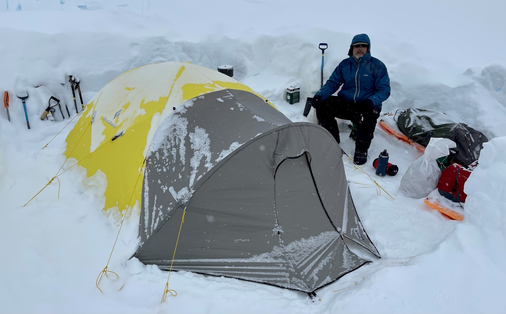 John MacDonald at a snow-covered camp, with tent and supplies, en route to the summit of Denali alt