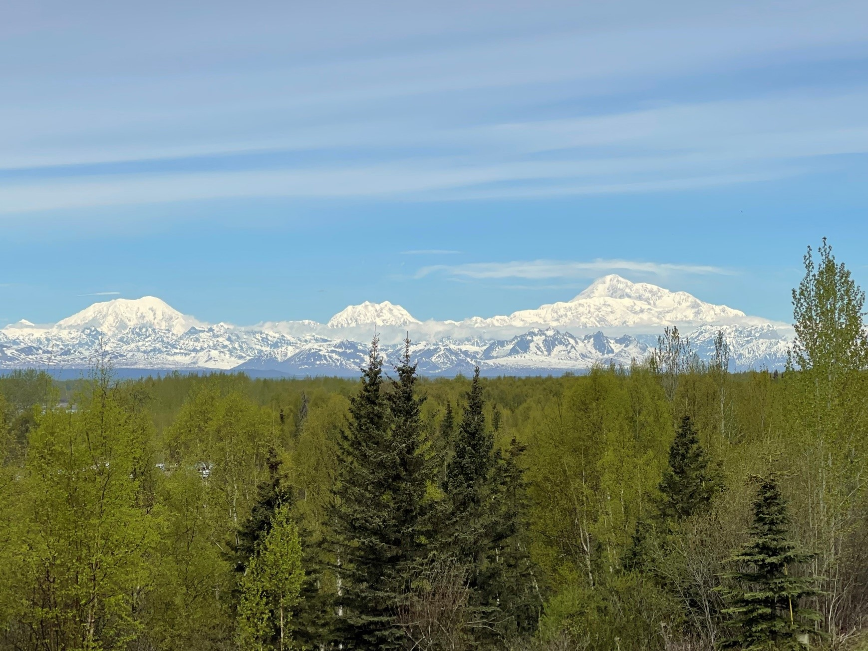 A breathtaking view of snowcapped Mount Foraker, Mount Hunter, and Denali alt
