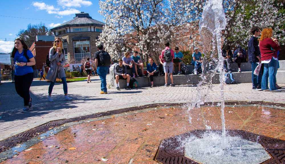 WPI students walk around the fountain on a sunny day.