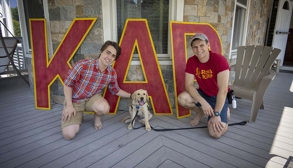 Two fraternity brothers pose with Leo, their new guide dog puppy in training.
