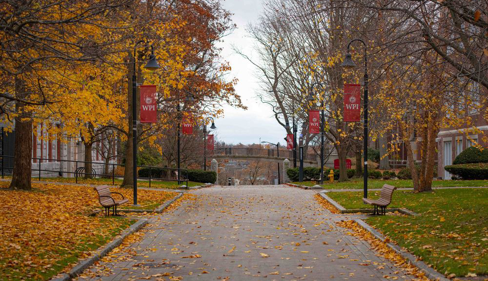 View of walkway on Campus, WPI banners and benches in a fall setting