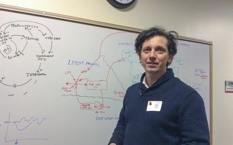 Dr. Oleg Pavlov standing in front of a whiteboard