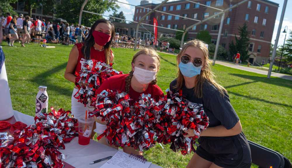 Three members of the cheerleading club pose with their pom-poms during the activities fair on the Quad.