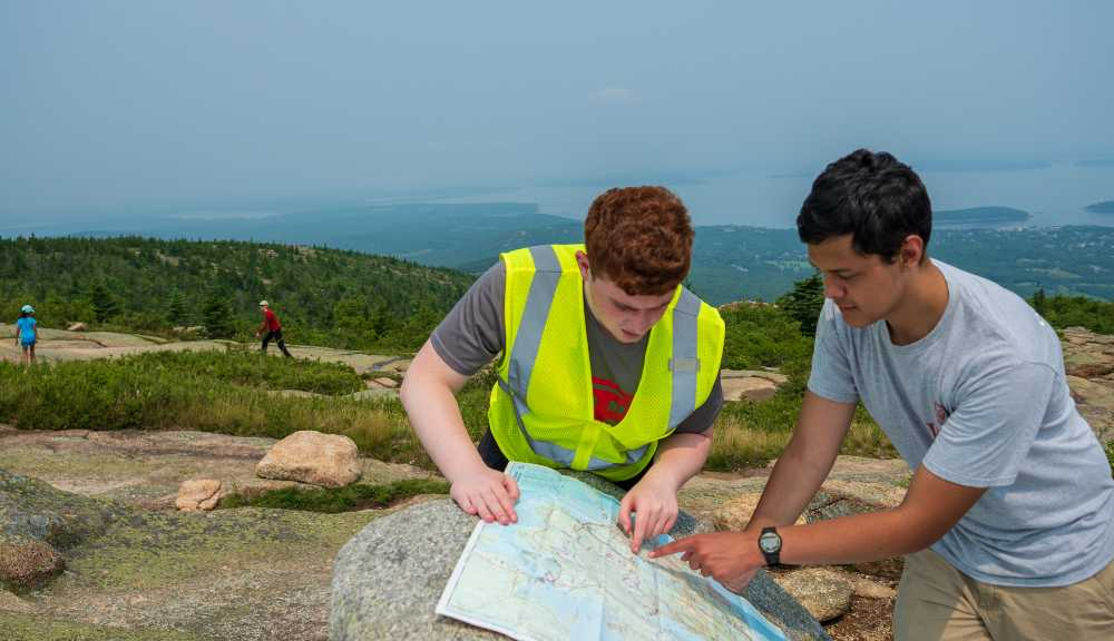 Two students study a map resting on a boulder in Acadia National Park.