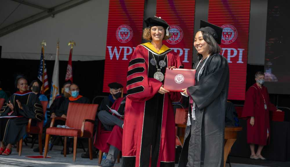 President Leshin poses with a Class of 2020 graduate onstage.