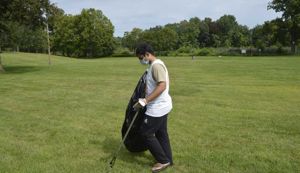 A student participates in a community service project in Institute Park.