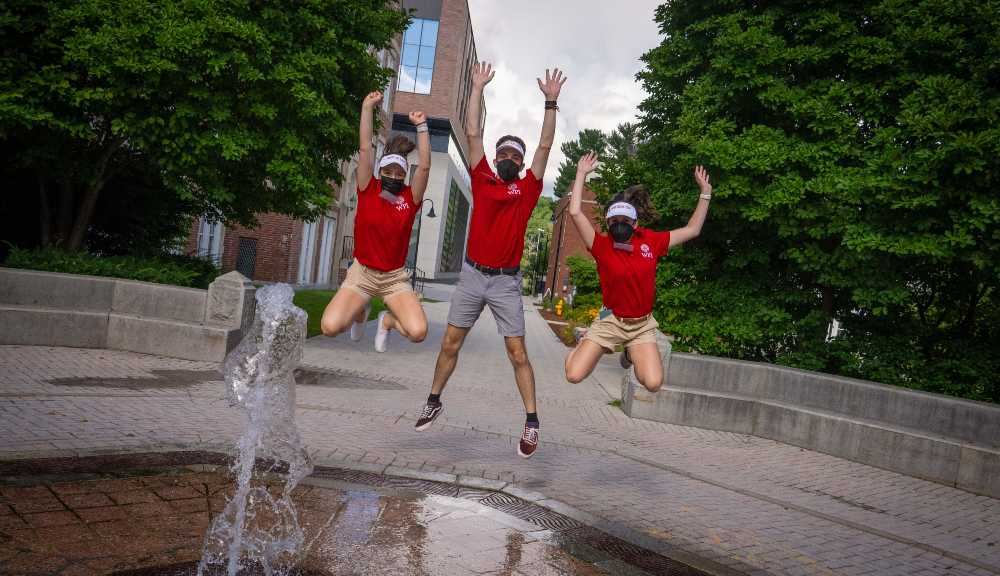 Three orientation leaders jump in unison behind the fountain.
