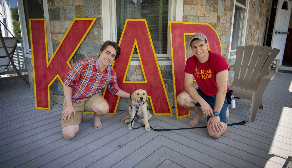 Two brothers of Phi Kappa Theta smile with their newest guide dog in training, Leo.