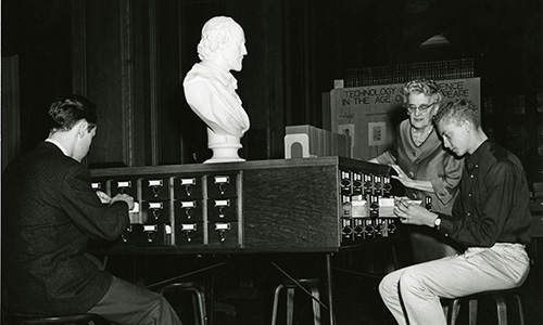 3 people going through older files with a statue on the table