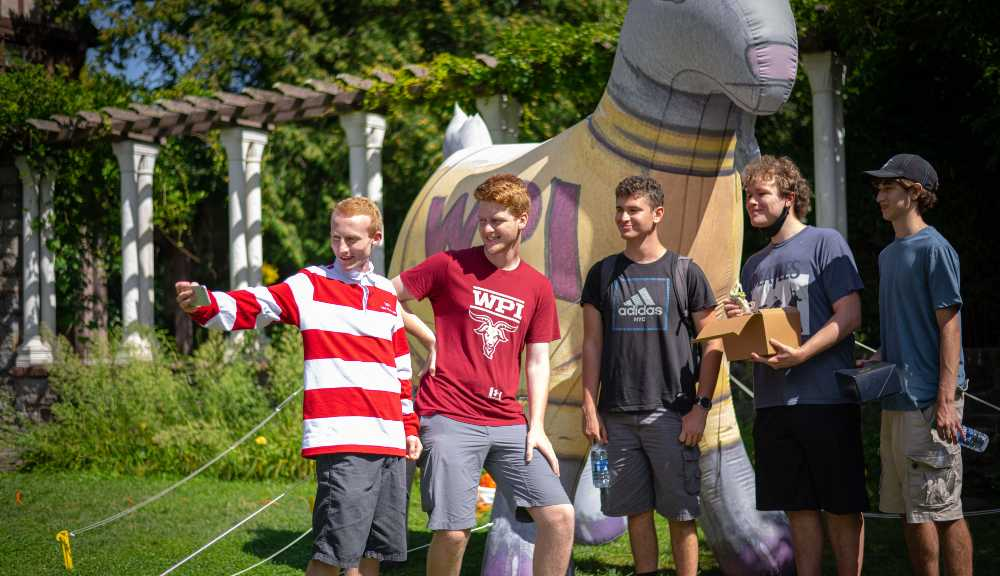 A group of new friends pose for a selfie in front of an inflatable Gompei.