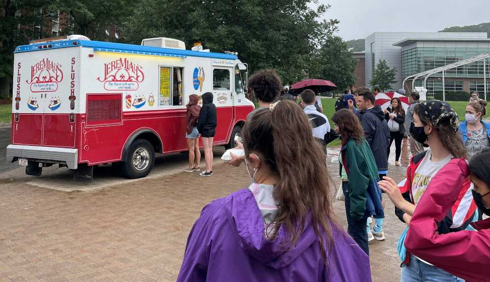 Students gather in line for soft serve ice cream in front of an ice cream truck.