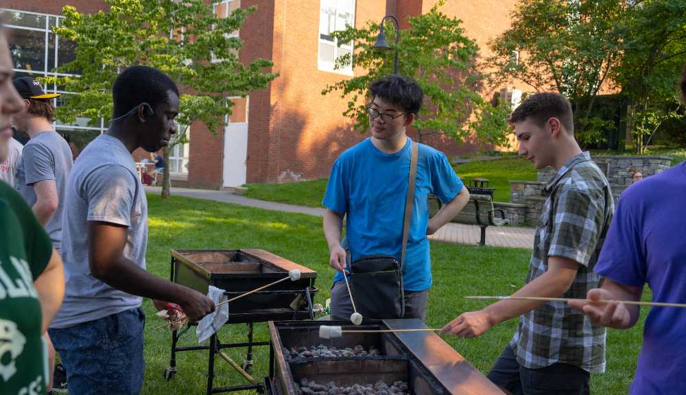 Students gather around a grill and make s'mores.