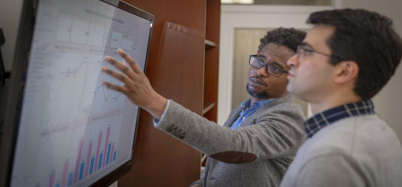 Professor examines graphs and data with his students