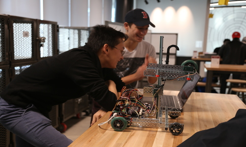 two students working on a robotic device on a tabletop are in the Innovation Center