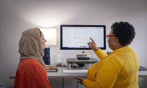 two women looking at a computer screen with one pointing at the image