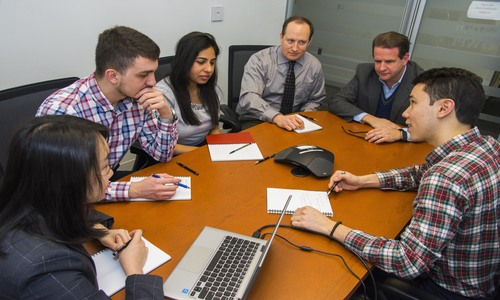 students and faculty sitting at a conference table with a phone in the middle