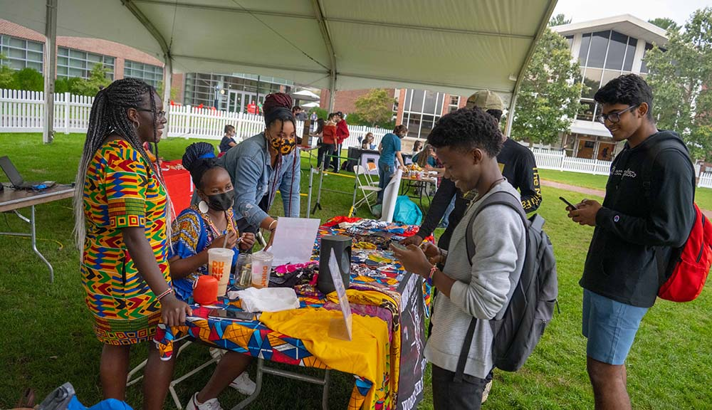 Students smile and laugh together at a table for the African Students Association club on campus.