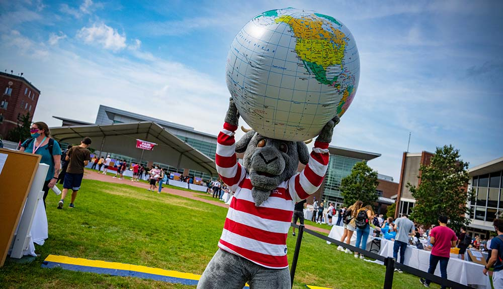 Gompei holds up a giant inflatable globe during the Global Fair on the Quad.