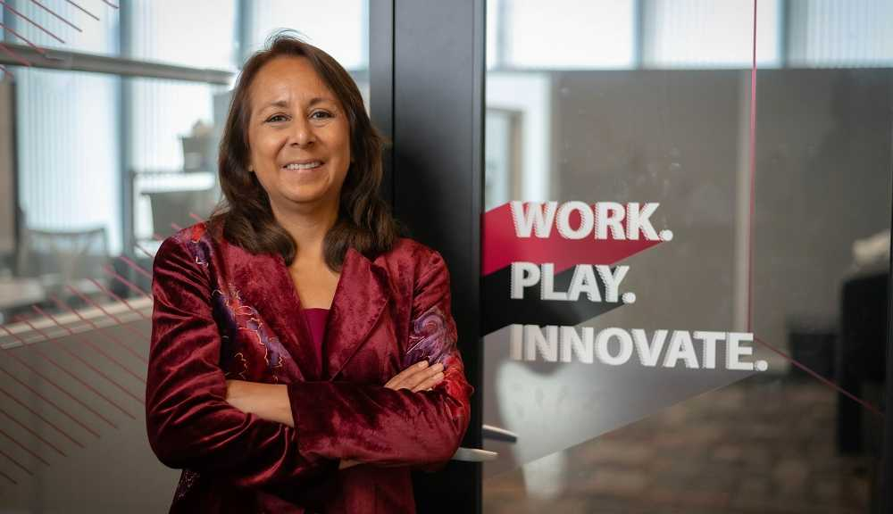 """Rosanna Garcia smiles for the camera in front of a window that reads """"Work. Play. Innovate."""""""