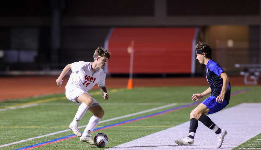 A WPI soccer player dribbles the ball while approaching a member of the opposing team during a game.