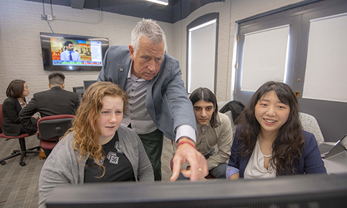 one professor with three students looking at a computer screen