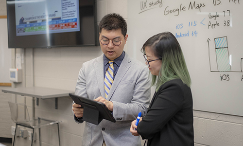 two students talking and looking at a tablet device