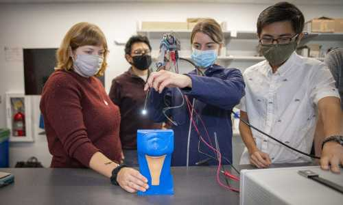 Students test the probe prototype on a plastic larynx in the lab.