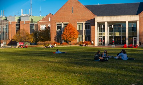 students sitting on the quad in front of Bartlett Center with fall trees