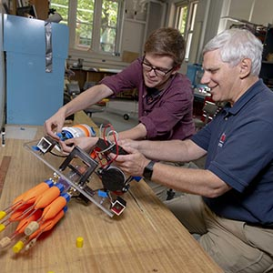Student working with professor on robot