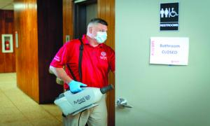 Man in a red WPI shirt wearing a mask and about to enter a room with a piece of equipment to mist