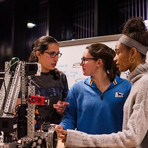 Three WPI female students with robot
