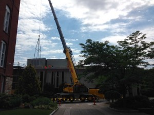 A crane lowers an air handling unit into place on the library roof yesterday.