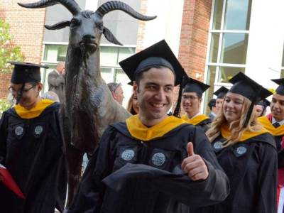 A student in a black robe gives the thumbs up as he passed the Proud Goat statue