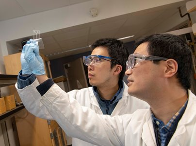 PhD candidate  Yundong Ren, right, and mechanical engineering professor Shawn Liu examine a microfluidic device designed to direct samples to the biosensor.