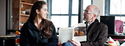 professor holding a book teaching a student