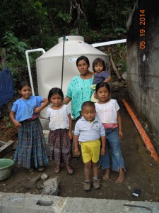A family stands in front of a new rainwater harvesting system—one of the eight the WPI team installed in May.