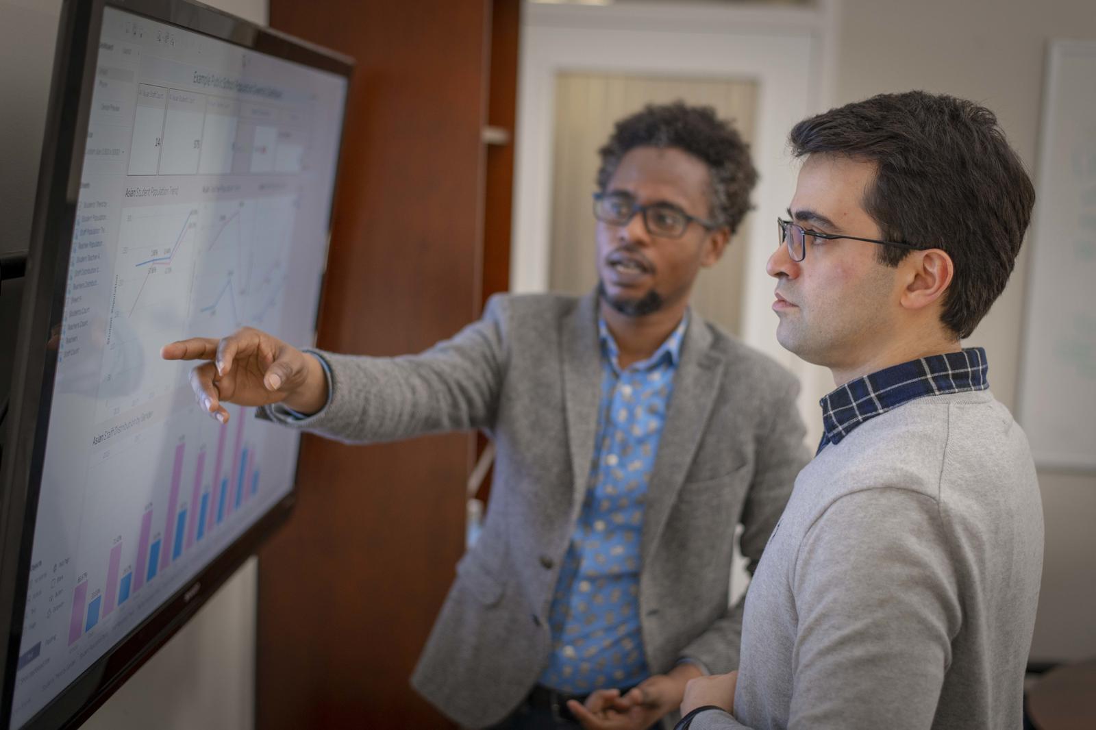 FinTech professor helps a student understand the presentation