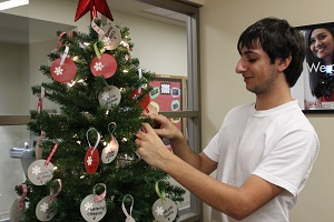 Marc Toomajian '17 hangs ornaments on the Giving Tree in the Office of Student Activities. Also assisting in the program are Daniela Ruiz '15, Xinyuan (Simon) Zhang '18 and Kyla Nicols '17.