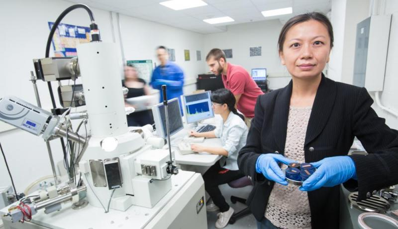 Jianyu Liang stands in the transmission electron microscope room holding a sample ready to be examined.