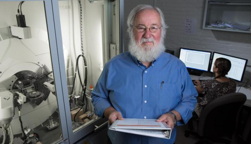 Richard Sisson, beside an x-ray diffraction instrument, faces the camera and holds a white binder
