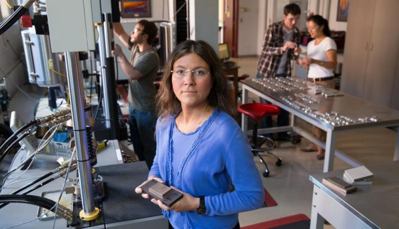 Diana Lados, in the materials testing laboratory, faces the camera and holds a part made with additive manufacturing