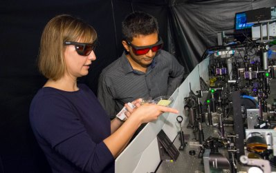 Lyubov Titova and Pratap Rao, both wearing red-tinted glasses, examine the terahertz spectroscope, a large box filled with lasers and instrumentation