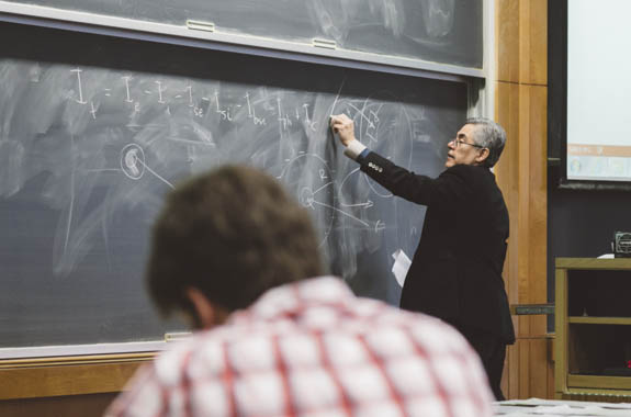 Student at lecture while professor writes on chalkboard